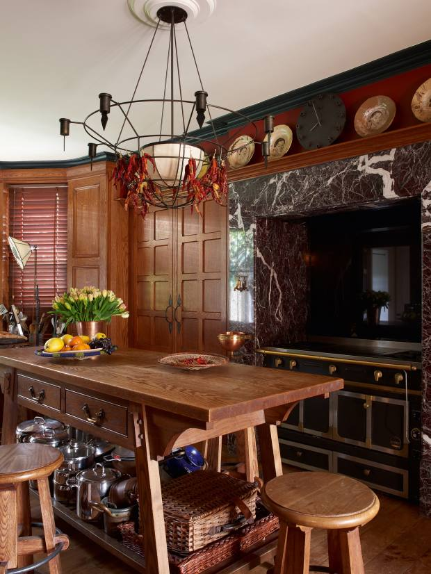 An Arts and Crafts vestry cabinet from an old vicarage forms an inglenook in this kitchen designed by Anthony Collett for his London home
