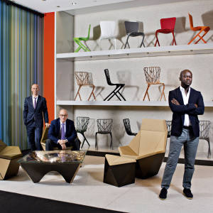 David Adjaye (on right) with Knoll CEO Andrew Cogan (standing) and design director Benjamin Pardo (seated). Adjaye's collection for Knoll includes, from far left, a low-back lounge chair, $6,250, a low table in cast bronze, $50,000, a high-back lounge chair, $7,500, an ottoman, $3,250, and a cantilevered chair in nylon (on top shelf), $300, and cast aluminium (on bottom two shelves), $490