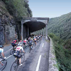Racing through an avalanche shelter in the Pyrenees, the Haute Route riders form an echelon to counter wind-resistance