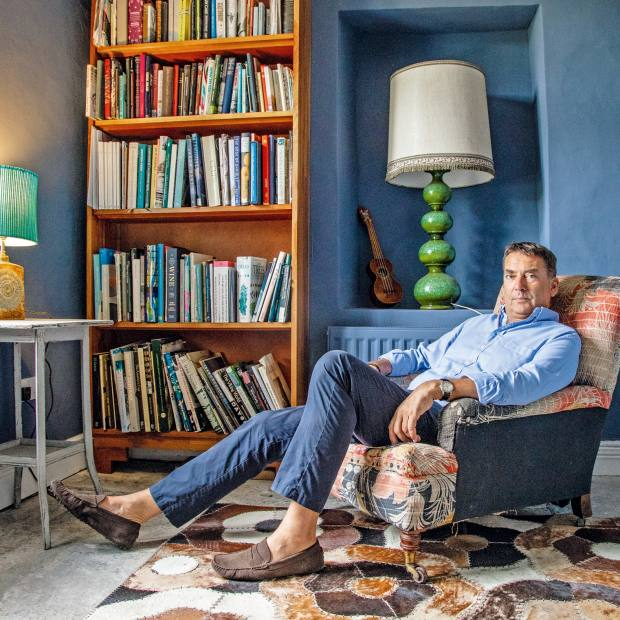 Bill Amberg in his study with the bookcase he designed to complement the Edward Bulmer navy-blue wall