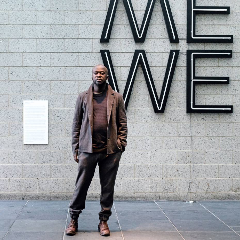 David Adjaye in front of a work by Glenn Ligon at The Studio Museum in Harlem