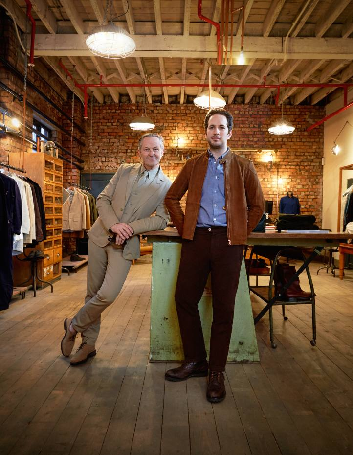 Private White VC's owner James Eden (on right), wearing its suede Rainrider bomber jacket with silk lining, £1,250, and creative director Nick Ashley, wearing its seven-piece suit, in the shop at its Salford factory