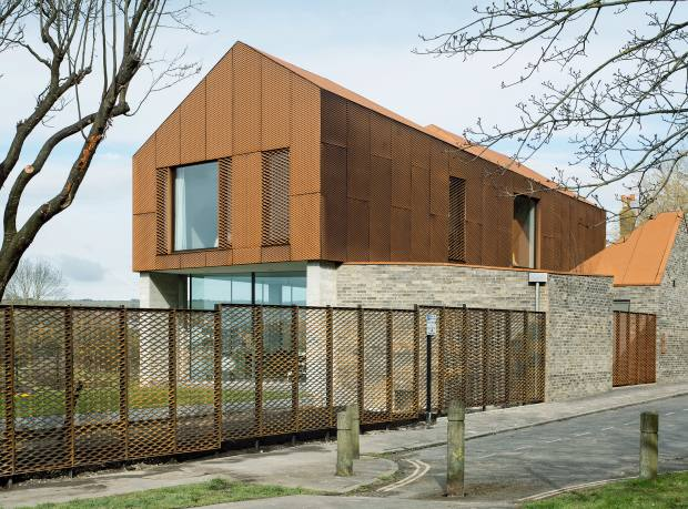 The Corten-clad upper storey of the Yeomans' home contrasts with a glass-walled lower level