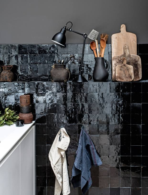 The kitchen in the Maison Hand Lyon apartment poses gloss black tiles and white cabinets against amid-toned grey wall
