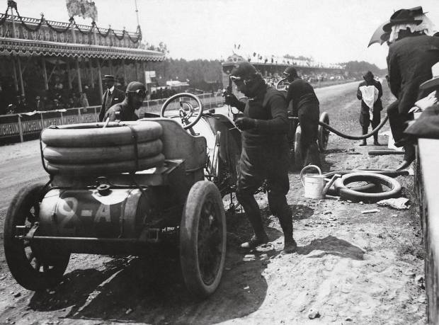 Vincenzo Lancia and his mechanic replenish their Fiat