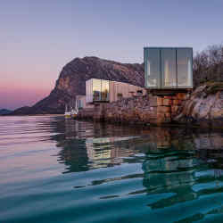 A quartet of cabins, designed by Snorre Stinessen, perch upon old stone quays on the Norwegian island of Manshausen