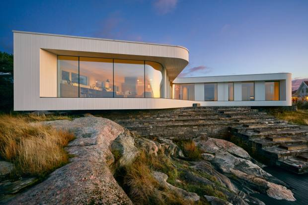 Villa AT by Saunders Architecture is perched on stone steps leading down to the water