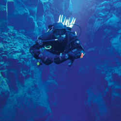 Dive guide Enno Ackermann swimming between tectonic plates in the glacial waters