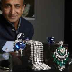 Viren Bhagat at the Symbolic & Chase stand at Masterpiece London, pictured with his creations (from near right): a sapphire and diamond lotus-design brooch, £542,000, a diamond bracelet, £115,000, a sapphire and diamond ring, £375,000, and emerald and diamond earrings, £313,000