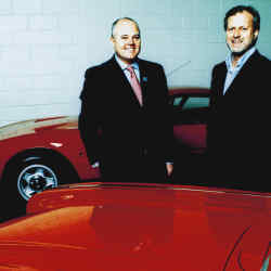"""James Knight (far left) and Tom Alexander at Olympia last December. In the foreground is a 1962 Chevrolet Corvettte Roadster; in the background a 1970 Ferrari 365GTB/4 """"Daytona""""."""