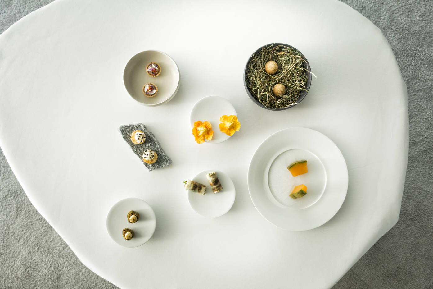 """A variety of appetisers, including """"pralines"""" of poularde, like two little eggs in a nest of hay; rounds of celeriac with crunchy, lemony ants; and Jerusalem artichokes topped with flakes of the chef's air-dried beef"""