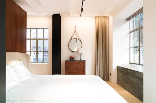An Adnet mirror hangs in a bedroom suite
