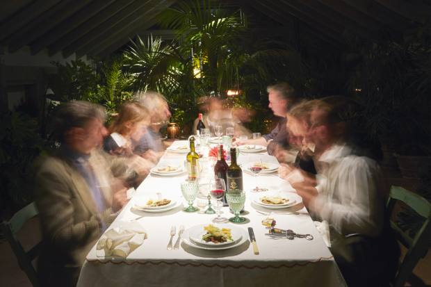 Guests eating dinner in the gardens by candlelight
