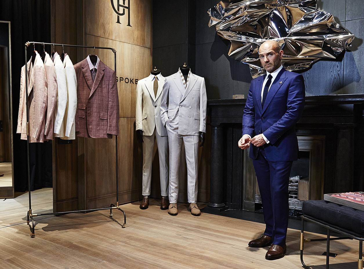 Gieves & Hawkes creative director Jason Basmajian at the brand's Savile Row flagship with suits from his spring/summer 2014 collection