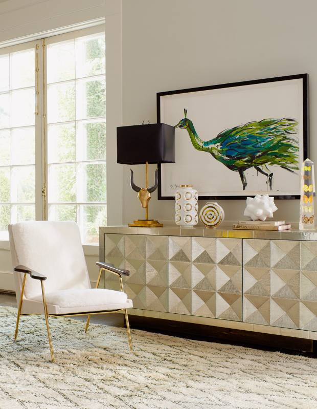 Jonathan Adler brass Pablo lamp with hand-painted paper shade, £895, brass and metal Talitha credenza, £3,950, and brass and shearling Ingmar chair, £2,250
