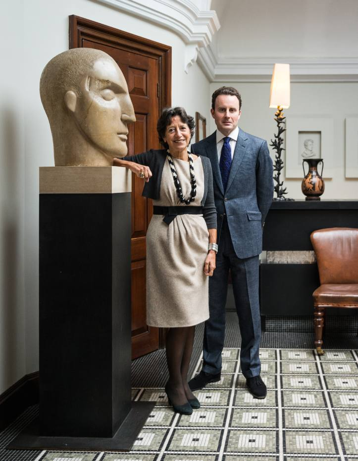 Olga Polizzi and antiquities and curiosities dealer Craig Finch at Brown's Hotel, Mayfair, next to a stone head by Emily Young. Background: a 4th-century BC Ancient Greek Apulian red‑figure pelike