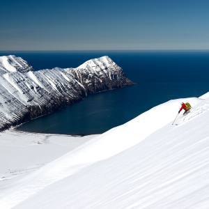 A Deplar Farm guest heli-skiing from a mountain top all the way to the Greenland Sea below