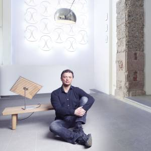 Piero Gandini at the Flos showroom in Milan, with (clockwise from far left) a Philippe Starck limited-edition Light Photon table lamp, €3,500, Wallpiercing, from £1,375, by Ron Gilad, and an Arco LED lamp, £1,722