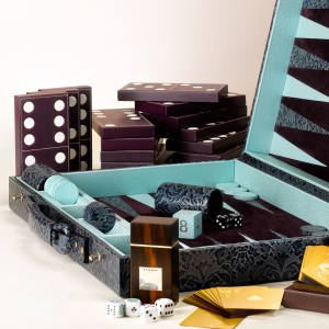Clockwise from below: Asprey calf-leather carpet dominoes, £1,100. Pickett damask-embossed leather backgammon set, £1,025. Linley Macassar ebony dice box with poker and standard dice, £245. Dunhill gold playing cards, £825. See text for stockists.