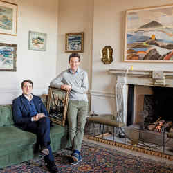 Wentworth Beaumont (left) and Hugo Burge (holding Back of Kirkcudbright by Ernest Archibald Taylor) in the drawing room at Marchmont House with (clockwise from bottom left) Iona by John Maclauchlan Milne, Eyemouth by Anne Redpath, North Ends of Iona by John Guthrie Spence Smith, Ben More from the North Shore, Iona by Samuel Peploe, and Large Highland Landscape by Rory McEwen