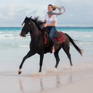 India Hicks riding on one of Harbour Island's pink sand beaches
