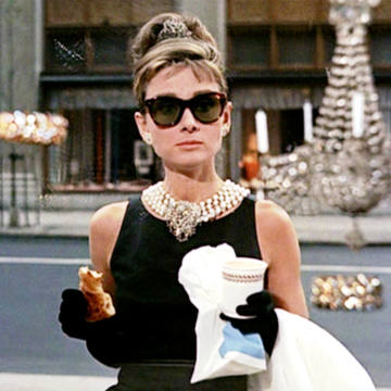 Holly Golightly, played by Audrey Hepburn, enjoys coffee and a croissant in Breakfast at Tiffany's