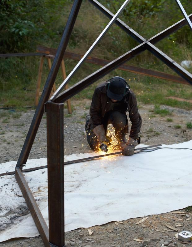 Oscar Tuazon welding a steel frame in Olympic Peninsula, Washington