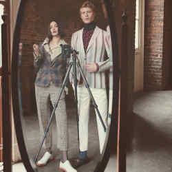 He wears Thom Browne polyester-mix coat, £2,180. Daks acetate/silk shirt, £265. Ralph Lauren Purple Label silk tie, £175. She wears Jil Sander cotton blanket (worn as shawl), £920. Erdem cotton-mix Albertcoat, £2,095. Daks silkshirt, £195