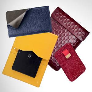 Clockwise from top left: Smythson deerskin Spencer smartphone folder, £150. Azzedine Alaïa leather iPad pouch, £595. Jimmy Choo glitter-finish canvas Trent iPhone sleeve, £135. Valextra calfskin BlackBerry PlayBook cover, £250