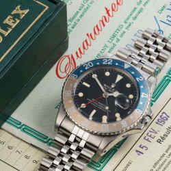 A vintage Rolex GMT-Master, from 1967, with its original box and certificate. The bezel, a dyed anodised aluminium ring used to demarcate different time zones, has gently faded over the decades to a mellow salmon and powder blue colour. It would have been all too easy to have this replaced - in fact replacement was encouraged when a watch like this went in for service, making extant original examples all the more desirable.