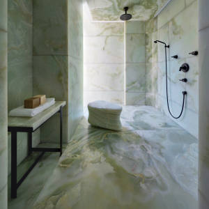In a Munich home, two giant blocks of green onyx were used to clad a capacious walk-in shower room, with modern black taps and fittings