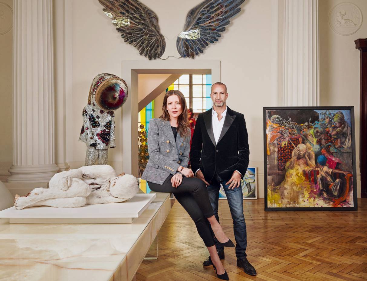 Deanna Leontieva and Rami Fustok at his London home with, clockwise from above left: Feather Child 1 by Lucy Glendinning, £12,000; Soundsuit by Nick Cave, $100,000; wings made of strips of paper by Greek artist Pavlos Dionyssopoulos, €160,000; and a commission by Jonas Burgert, €80,000