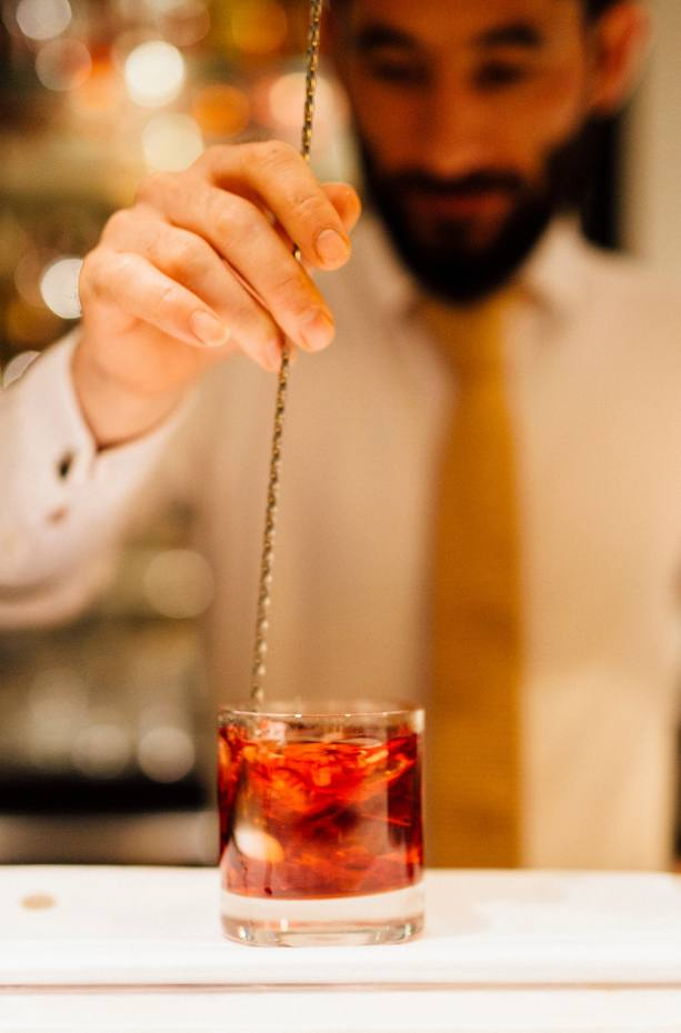 A bartender mixing a Negroni cocktail in the Blue Bar at Quo Vadis for the Soho Negroni Championships