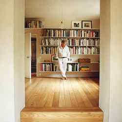 John Pawson in his library with the floating aluminium shelves he designed to give prominence to the books