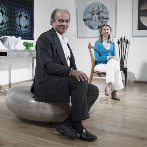 Patrick Fauchier sits on a McCollin Bryan Coffee Bean coffee table; Liliane Fawcett sits on a Hans Wegner Valet Chair, at Themes & Variations, London. On wall (from left): Victor Vasarely and Pinton Frères for Tapisserie d'Aubusson Stri-Arc tapestry. Us 01 C-print photograph and Someday, Somewhere – II C-print photograph (just seen), both by Liu Ren. On table (from left): Toots Zynsky glass vase, £15,000. Christian Astuguevieille Rope Coupe. Against wall: Tom Dixon Railings chair