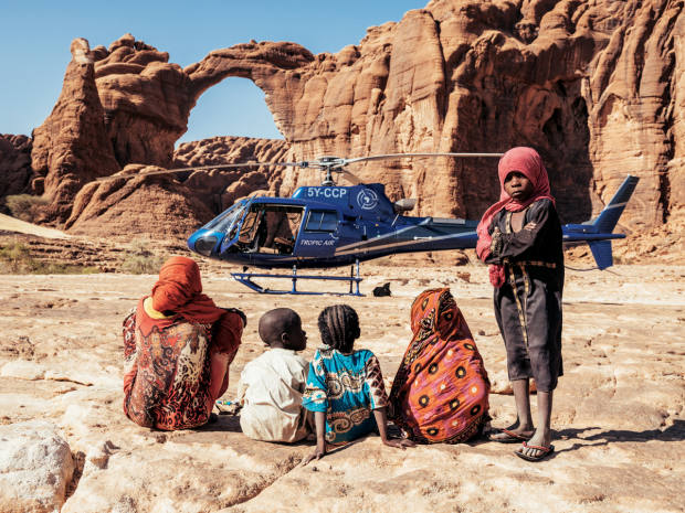Tropic Air Kenya's helicopter in front of Aloba Arch, with a group of local Bideyat children