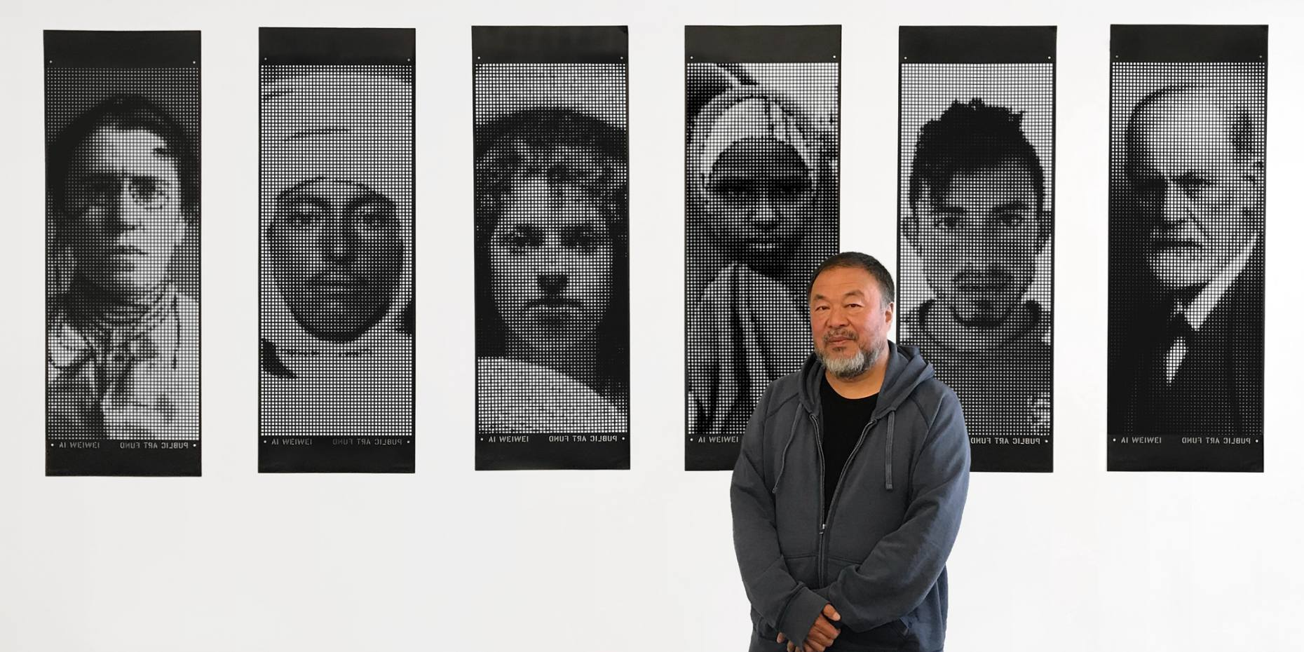 Ai Weiwei with portraits from his Good Fences Make Good Neighbours exhibition