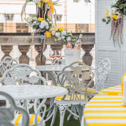 The Au Soleil Balcony is an urban retreat in the heart of London, filled with garlands of flowers and dressed with chairs and banquettes in chic yellow stripes, designed to evoke the spirit of the French Riviera
