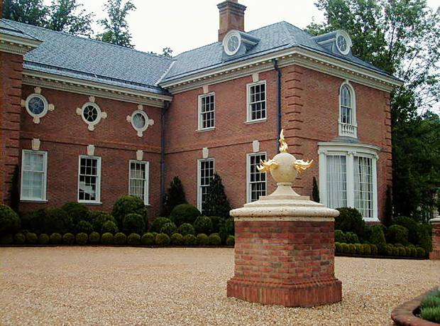 A raised gravel forecourt in Virginia designed by George Carter, with box and yew topiary and a brick pier with a stone ball and gilded-lead flame