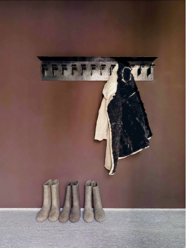 The entrance to the Baltics house sees bitter-chocolate walls highlighted by a vintage patinated-iron Robert Mallet‑Stevens coat rack