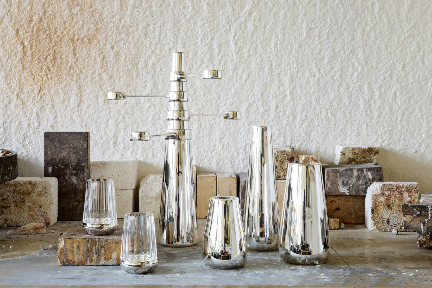 From far left: E&Co x Christopher Jenner silver-plated Bounce Crystal votives, £280each, silver‑plated Kinetic Monolith candelabra, £2,200,and small, tall andmedium silver-plated Beacon candlesticks, £380,£450and£300