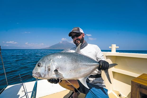 Fishing guide Jeff Forsee catches a giant trevally from the tender