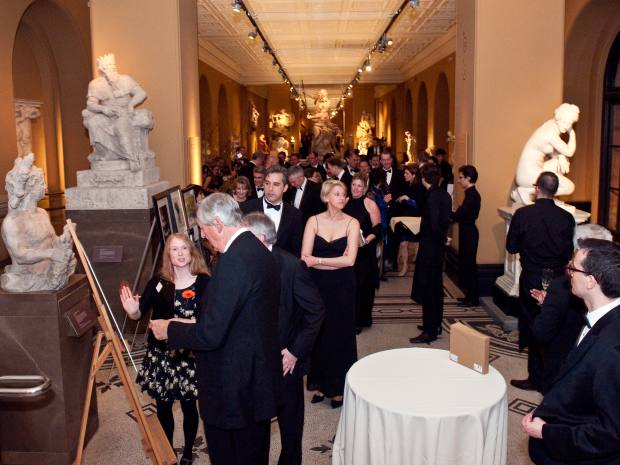 Guests admire artworks for sale at the gala