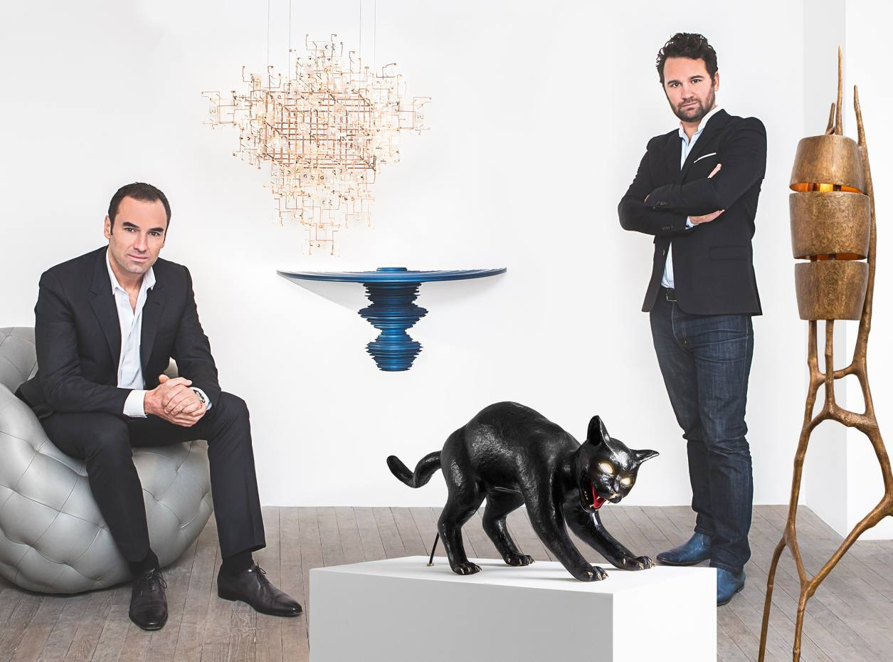 Carpenters Workshop Gallery owners Loïc Le Gaillard and Julien Lombrail with a Robert Stradler leather Spherical Bomb armchair, price on request, Studio Drift dandelion seed and bronze Fragile Future Diamond Chandelier, price on request, Sebastian Brajkovic anodised aluminium console table, from £4,500, Studio Jon bronze, handblown glass and hand painted Cat Hiss lamp, from £10,000, and Charles Trevelyan bronze Tripartite floor lamp, from £9,500