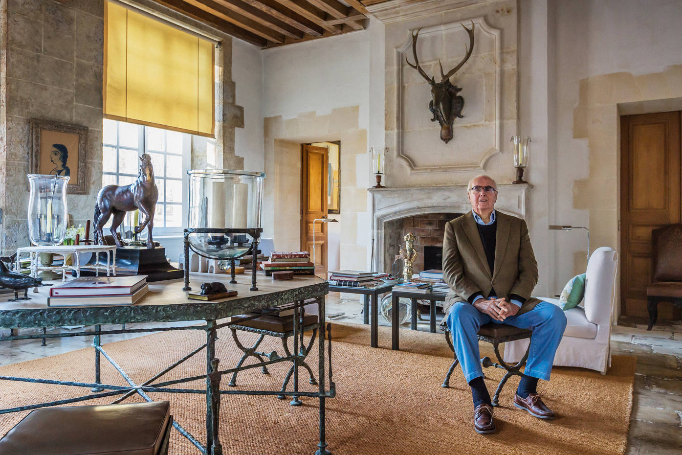 Hubert de Givenchy at the Manoir du Jonchet, his home a couple of hours south-east of Paris, with a Diego Giacometti bronze and oak Table Octogonale aux Caryatides et Atlantes, estimate £700,000-£1m, bronze and glass Paire de Photophores tealight holders (on table), £140,000-£170,000, andbronze and leather Ensemble de Quatre Tabourets en X Troisième Version stools, £270,000-£430,000