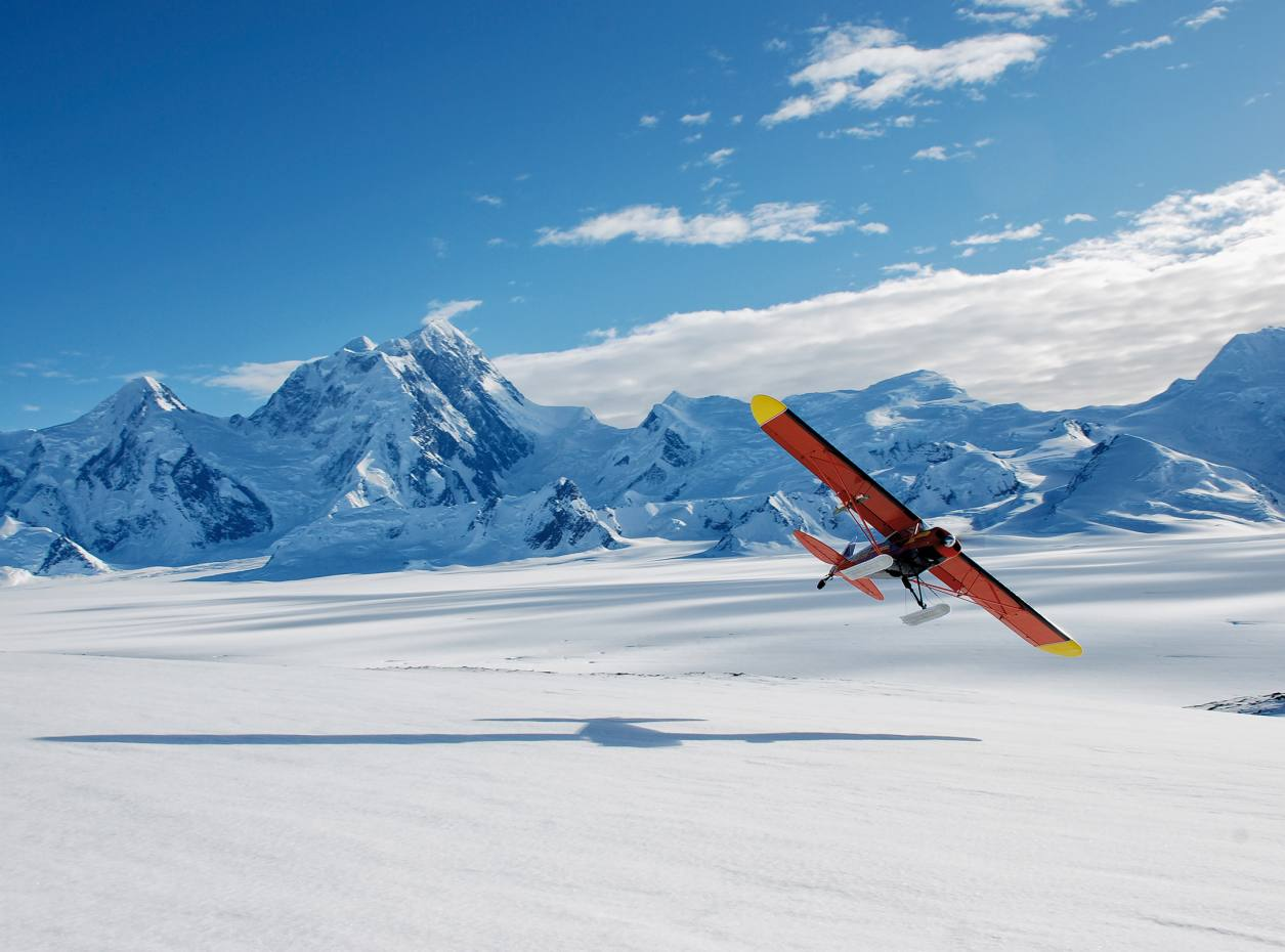 One of Ultima Thule Lodge's Piper Super Cubs flies over Alaska's Bagley Icefield glacier with Mount St Elias in the background