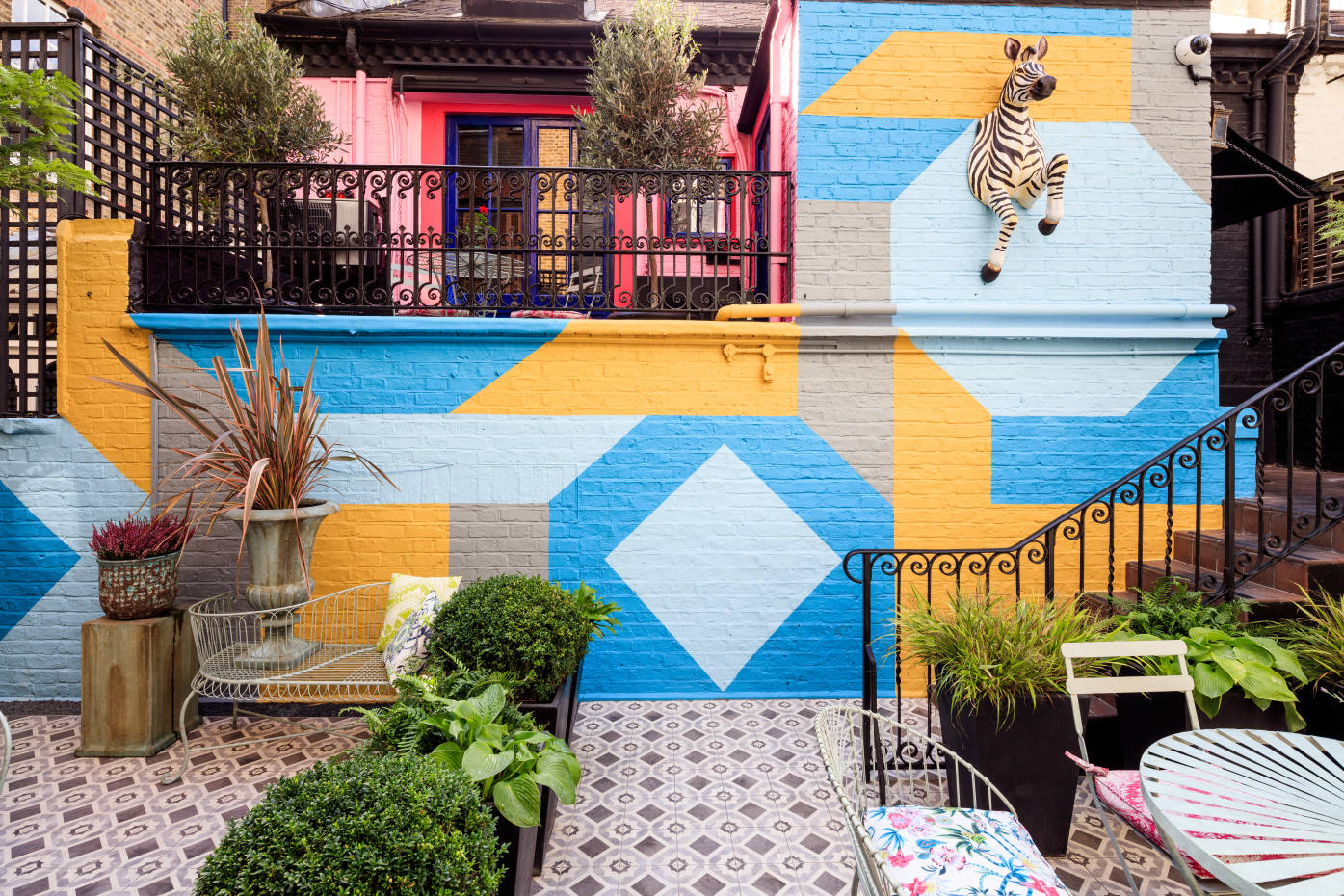 A yellow-and-blue mural creates a bold backdrop in the Blakes Hotel garden