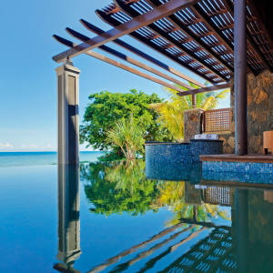 A beachfront suite at Angsana Balaclava, with an outdoor sitting room and an L-shaped infinity pool