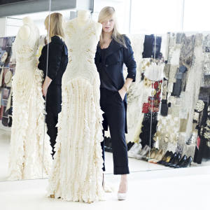 Sarah Burton stands with an Alexander McQueen ivory pearl embroidered gown at the company's London offices.