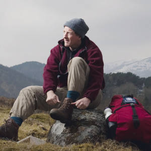 James Henderson takes time out for a snack and a new pair of socks, snowcapped Carn Dubh behind.